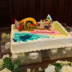 リバティ・ウエディング アプロッシュ:グアム挙式のムービーを流し、海をイメージしたブルーシャンパンで乾杯!ケーキもテーマに沿ったオリジナル