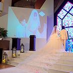 ウエディング パルコ アルジェント:ブルーのステンドグラスと白大理石が神聖な雰囲気。スクリーンに映し出される誓いのシーンに感動が広がった