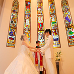 セントポーリア教会 シャルム・ド・ナチュール:温かみのある木の色、ステンドグラスの輝き、生演奏が感動を彩る。挙式後は室内階段でのフラワーシャワーも