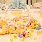 セントポーリア教会 シャルム・ド・ナチュール:丸いガラス瓶&明るいオレンジカラーの装花が白い空間にマッチ。評判のフレンチコースで美味しいおもてなし