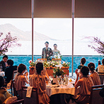 AMANDAN CALM(アマンダンカルム):海の色に映えるネイビーのドレスにお色直しをしてテラスから入場。友人や新郎からのサプライズに感激