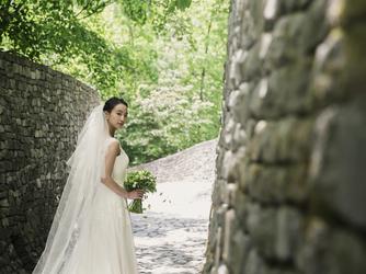 石の教会 内村鑑三記念堂:ドレス姿が一層美しく映える石畳の回廊。清らかな緑と石が調和する風景が、心を穏やかにしてくれる。