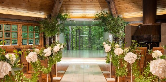 THE NIDOM RESORT WEDDING:扉が開くとふたりを迎えるのは、開放的な窓から広がる美しい森とその森の中にそびえたつ純白の十字架。ふたりはどこまでも続く広大な森へ向って永遠の愛を誓い合う