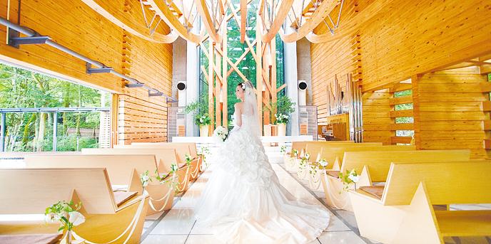 軽井沢クリークガーデン:豊かな自然を堪能できるガラスの透明感と森に溶け込む木の温かみが美しく融合したチャペル。正面の木のオブジェは手を取り支えあう新郎新婦を、カーブを描く天井の梁は二人の心を繋ぐ天使の弓を表現。