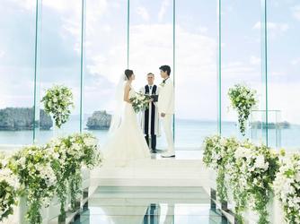 アイネス ヴィラノッツェ 沖縄:白く輝く空間の向こうに、青い空と海が広がる。左右のガラス壁奥には水が流れ、15mの天井高が開放感を演出