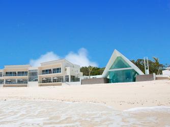 アイネス ヴィラノッツェ 沖縄:白砂のビーチフロントに立つ、透明感あふれるチャペル。隣のバンケット棟でゲストをもてなすパーティを
