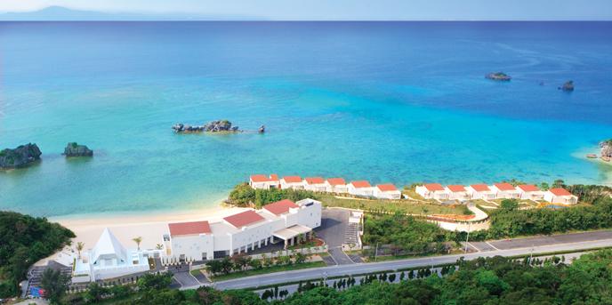 アイネス ヴィラノッツェ 沖縄:ビーチフロントに位置するウエディングリゾートの一画に建つチャペル(左)。陸地側から海に向かって高く伸びる屋根は、大空へ、そして未来へ羽ばたくための滑走路をイメージ。青い海を臨みながら永遠の愛を誓おう