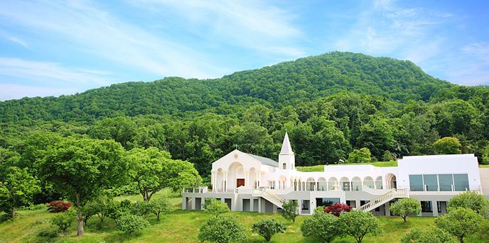 ローズガーデンクライスト教会:背後に迫る藻岩山の四季の美しさ、小鳥のさえずりや流れる雲の祝福を近くで受けられる絶好のロケーション。ふたりが大切な誓いをたてた教会は、時の流れの中でいつまでも美しくこの場所に在り続ける