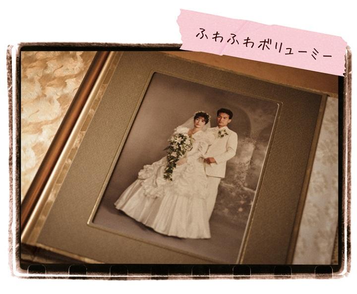 肩にボリュームがあるドレスを着た花嫁と花婿