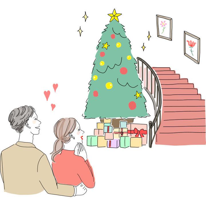 会場に飾られたクリスマスツリーを見つめるカップル