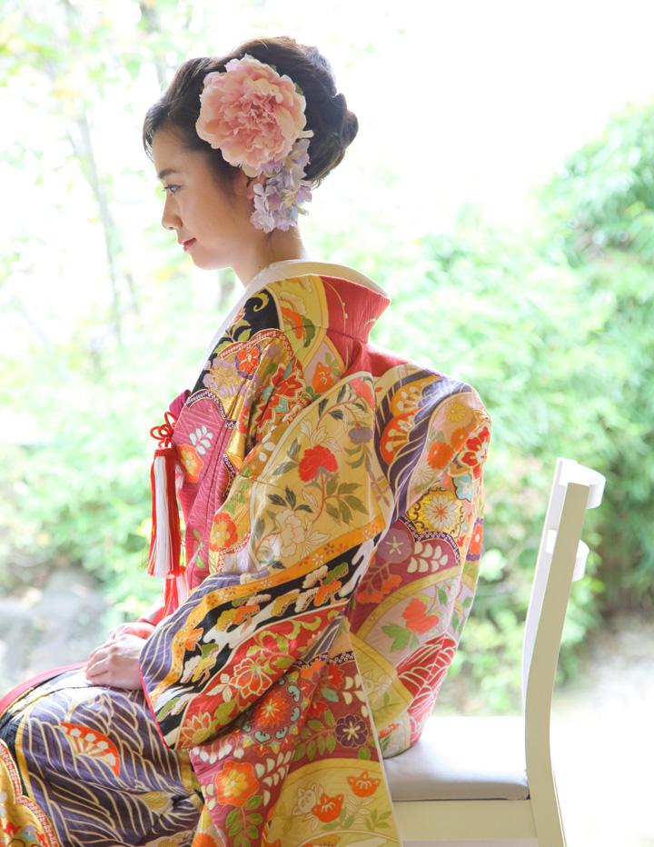 椅子に腰掛ける打掛姿の花嫁を横から見たところ