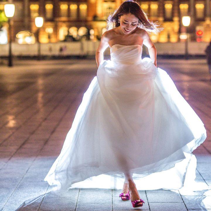 夜景で躍動感のあるポーズで赤いシューズを履いた花嫁