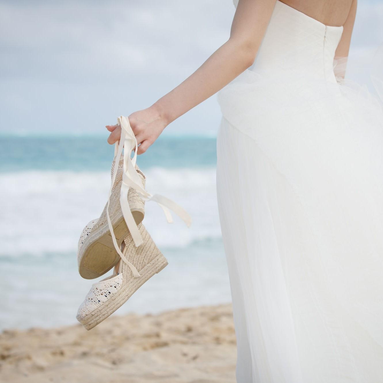 ビーチでウエッジソールシューズを手に持った花嫁の写真です