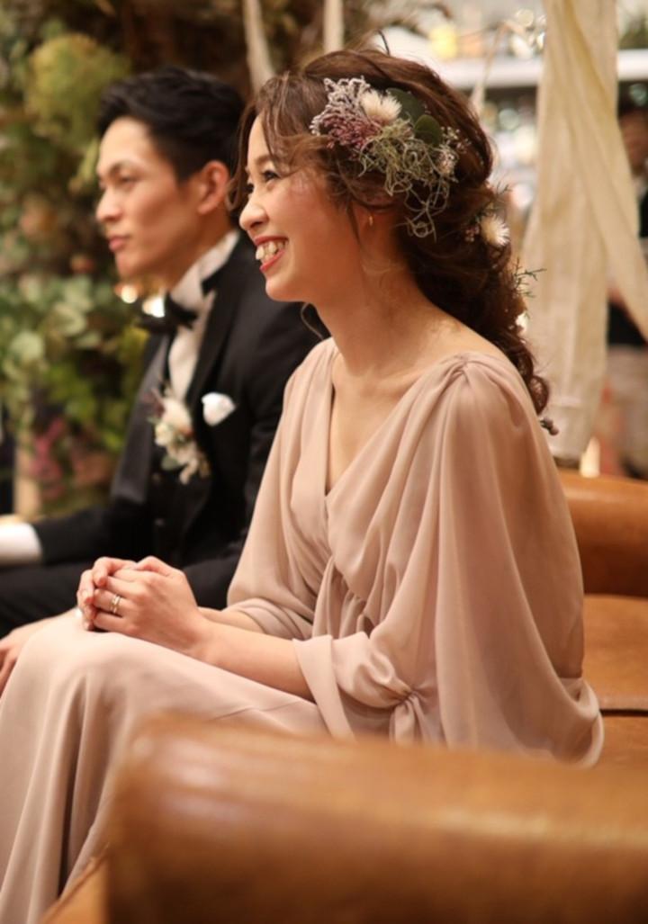 淡いピンクグレーのドレスはゆったりとしたドレープを描き、リラックスムード満点。装花にドライフラワーを使用した会場の雰囲気にもなじみ、ブーケもナチュラルな雰囲気の小ぶりサイズが今どき風の抜け感を演出して