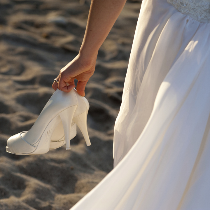 ウエディングシューズを手に砂浜を歩く花嫁の後ろ姿