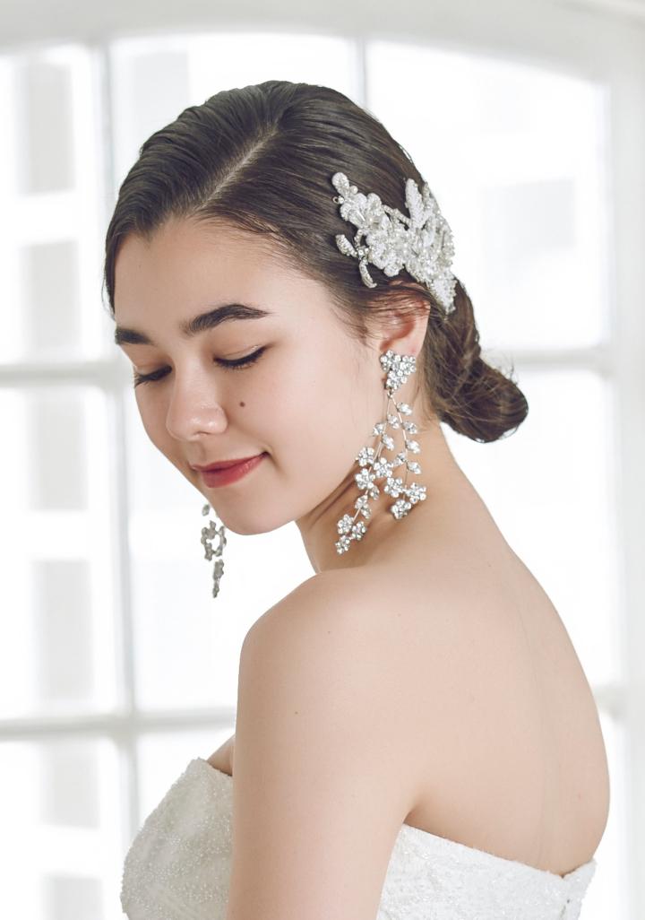 襟足でゆるっとまとめる「ローシニヨン」は、大人フェミニンに見せたい花嫁に人気。中でも最近は、スタイリッシュな小ぶりシニヨンやこなれて見える縦長シニヨンがトレンドIN! ゆるふわでも甘くなり過ぎないロー