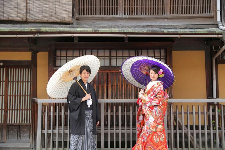 番傘をさして日本家屋をバックにたたずむ新郎新婦