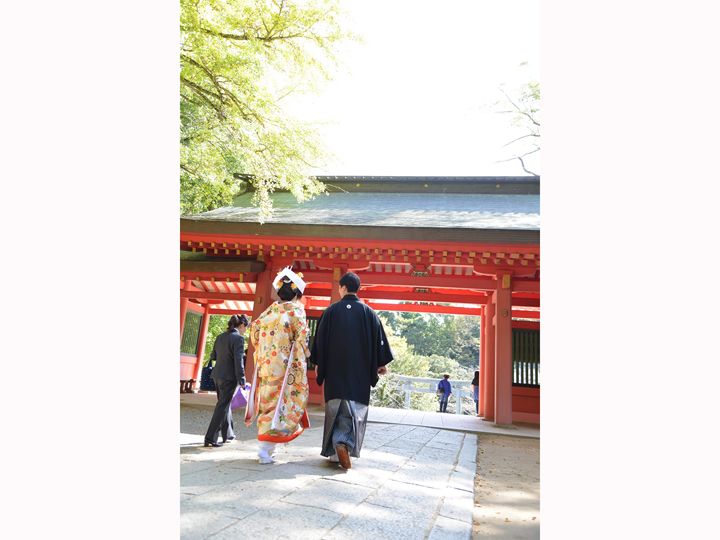 赤い塗りが美しい神社の山門へ向かって歩く和装のふたり