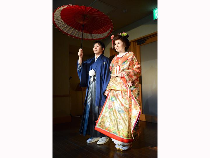 金色の色打ち掛けと青い紋付袴に番傘をさして入場する新郎新婦