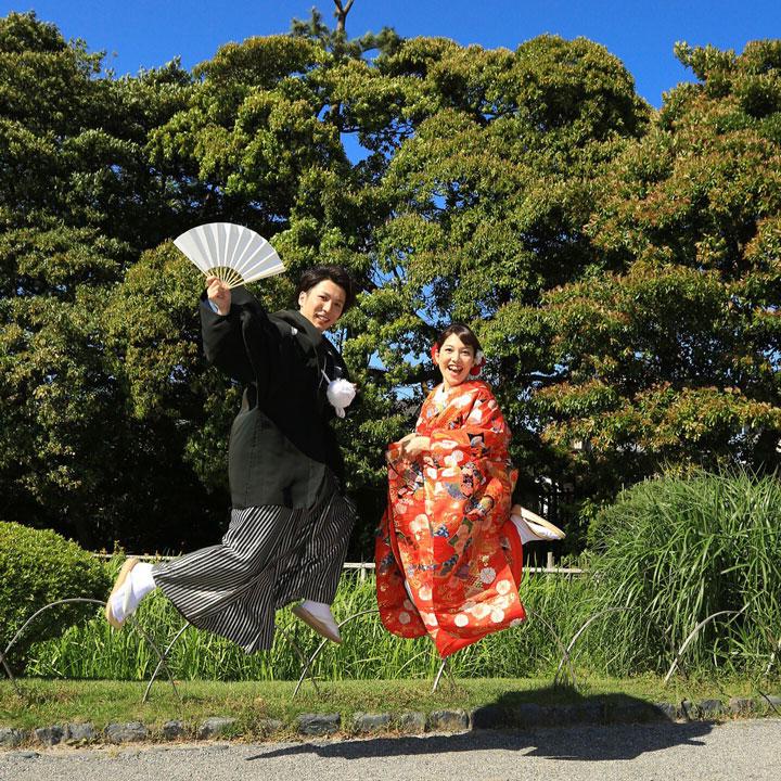 袴姿の新郎と色打掛姿の新婦が、青空の下で思いきりジャンプしています。