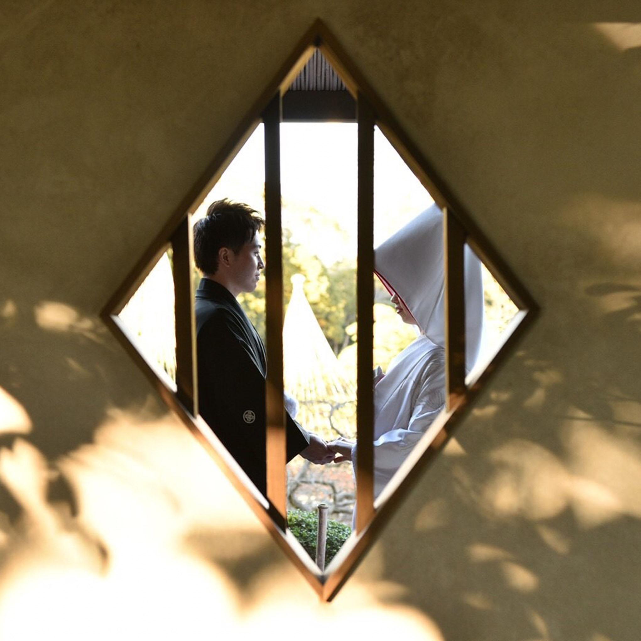 菱形の窓の向こうで、和装の新郎新婦が手を取り合い見つめ合っています。