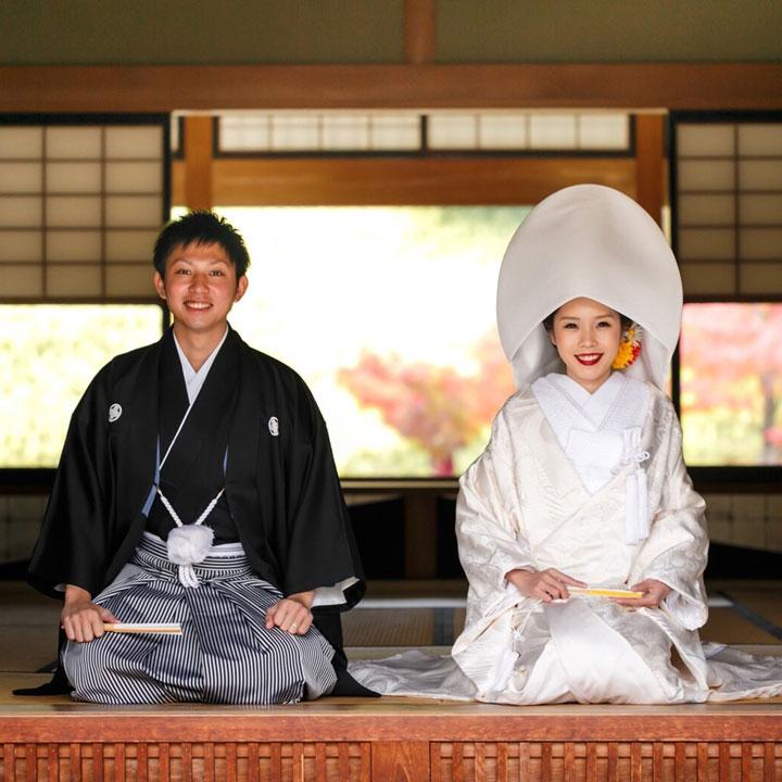 白無垢の花嫁と袴姿の花婿が正面に向かって正座しています