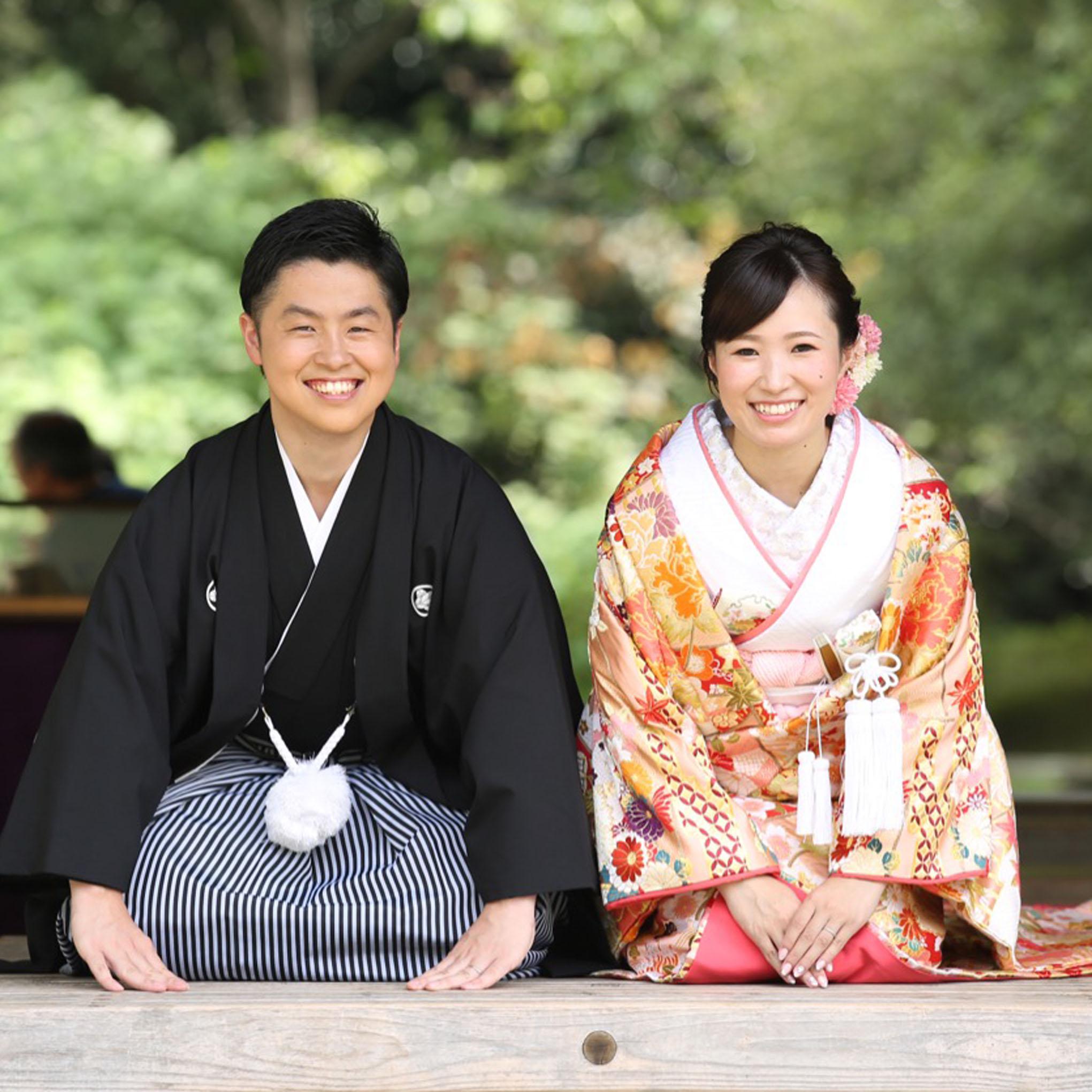 色打掛姿の花嫁と袴姿の花婿が正座で手をつき、正面に向かってご挨拶をしています。