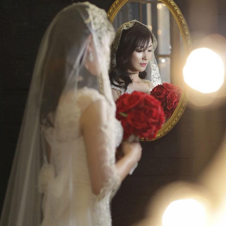 赤いバラのブーケを持ったウエディングドレス姿の女性が、鏡を前にたたずんでいます。