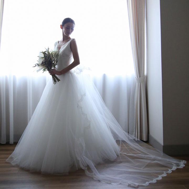 白いウエディングドレスでブーケを持った花嫁が、右下を見て少しうつむいたポーズでたたずんでいます。