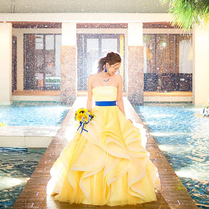 雨の降る中、黄色いカラードレスを着た女性がライトに照らされて、うつむいて立っています。