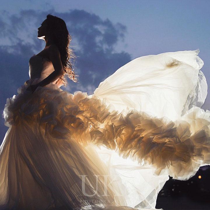 夕暮れ時のうす暗い背景に、ウエディングドレスを着た女性が横向きに立っています。