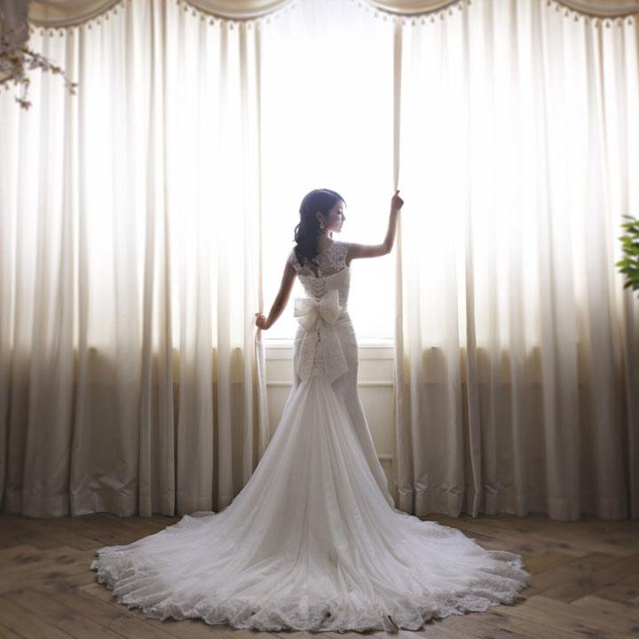 ウエディングドレスを着た女性が、カーテンのある窓辺で後ろ向きに立っています。