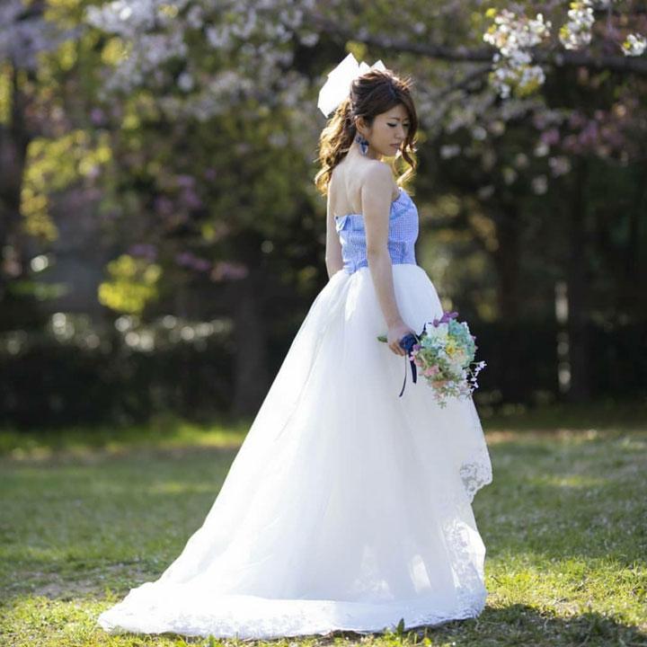 緑あふれる公園に、フィッシュテールドレスを着た花嫁がいます。