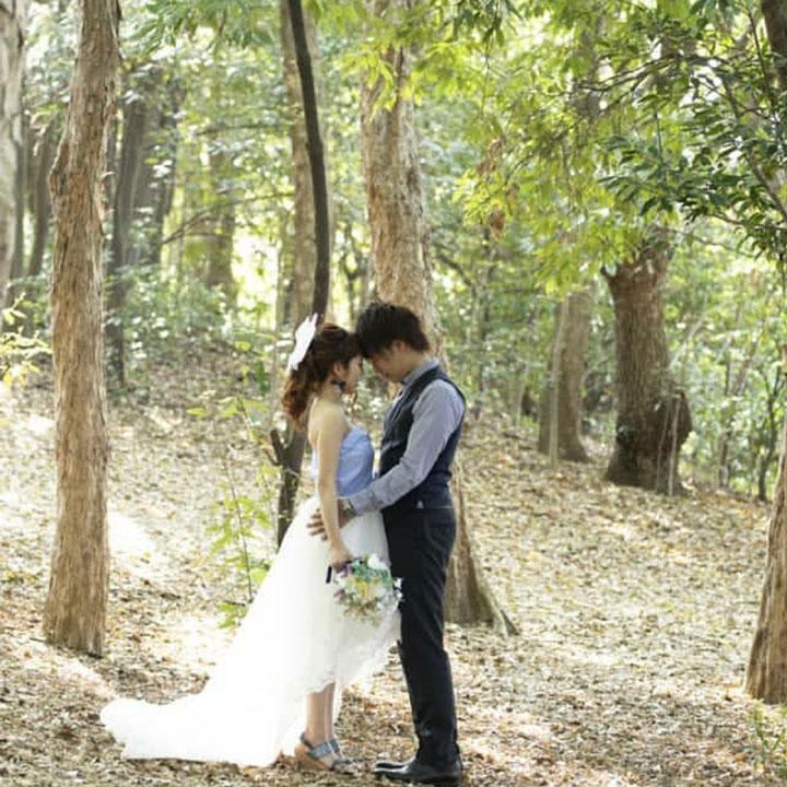 新郎とフィッシュテールドレス姿の新婦が森の中で向き合っています。