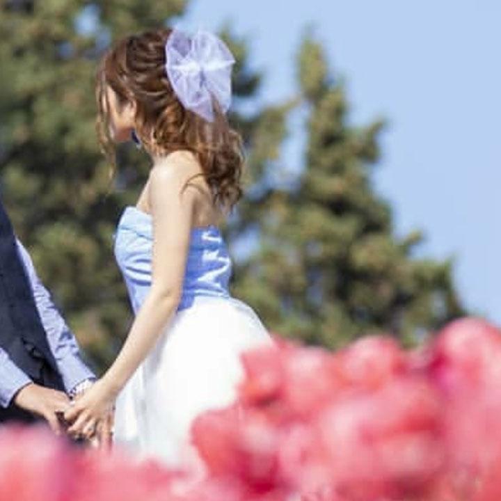 赤いお花畑の向こうにフィッシュテールドレス姿の花嫁がいます。