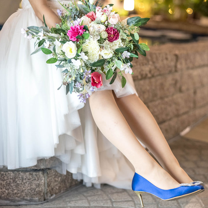 フィッシュテールドレスの足もとはブルーのパンプスです。