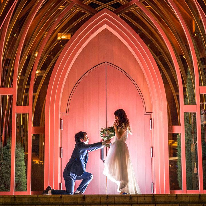 ひざまずいてプロポーズのポーズをする新郎と、フィッシュテールドレス姿の花嫁。