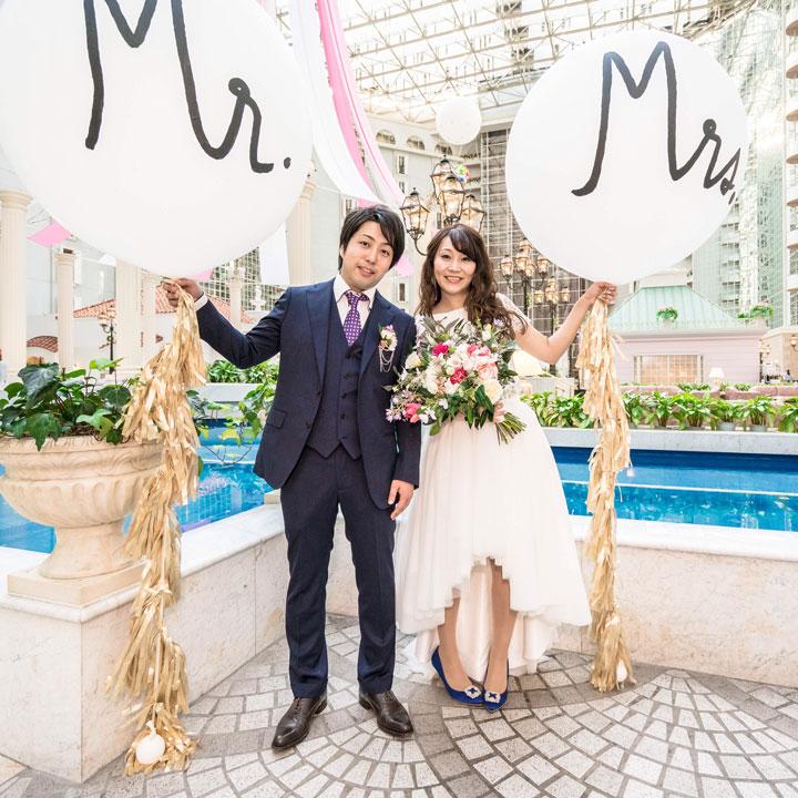 フィッシュテール姿の花嫁が、新郎とプールを背景に写真に写っています。