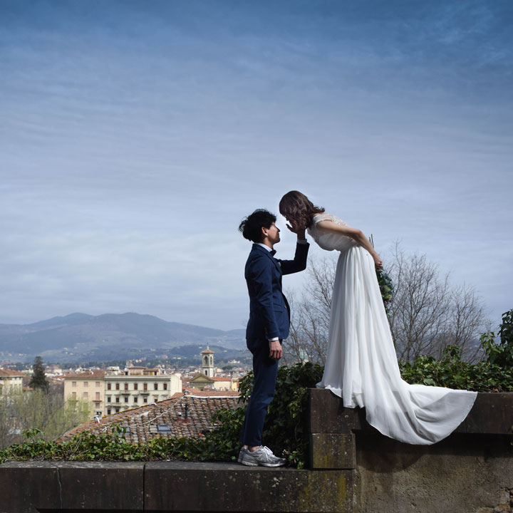 フィッシュテールドレスを着た新婦と新郎がフィレンツェの街にいます。