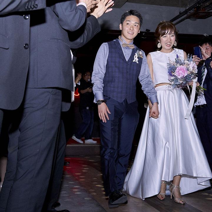 フィッシュテールのセパレートドレスを着た花嫁と、新郎が二次会の会場で腕を組んで歩き、ゲストが取り囲んでいます。