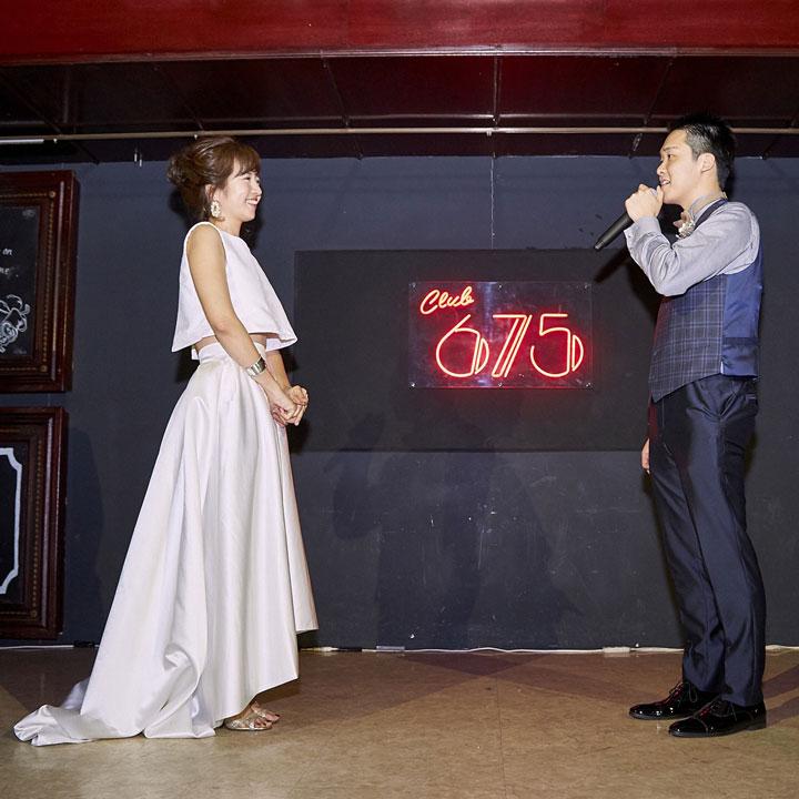 フィッシュテールのセパレートドレスを着た花嫁と、新郎が二次会の会場で向かい合っています。