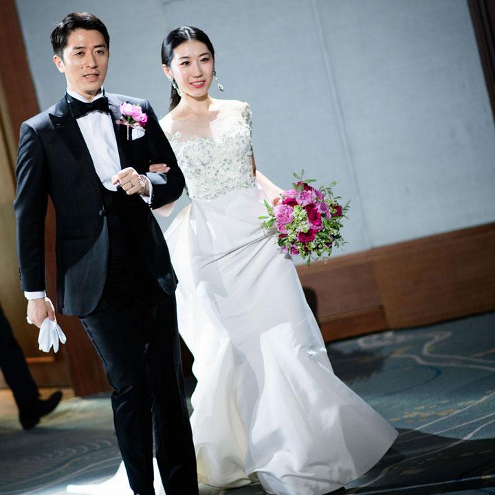 フラワー刺繍をほどこしたオフショルダードレスを着た花嫁