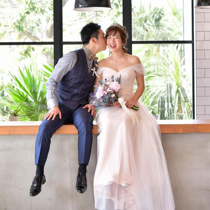 ペールピンクのチュールスリーブのオフショルダードレスを着た花嫁。