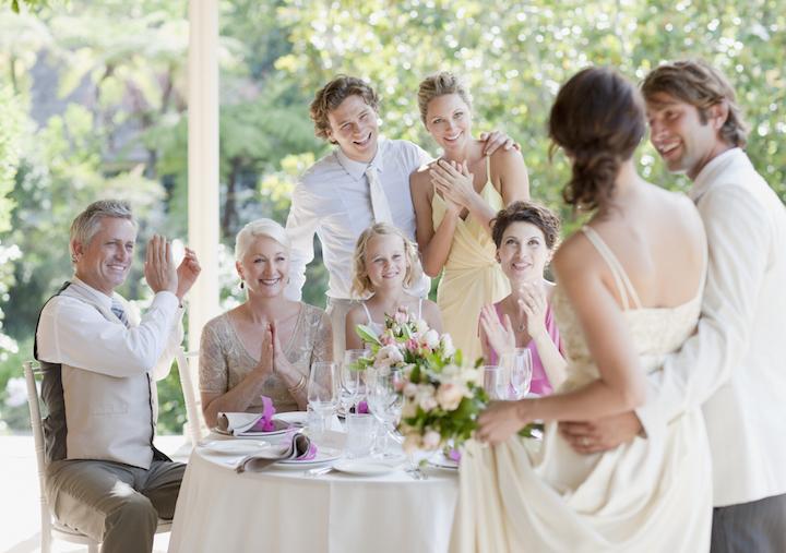 ゲスト卓に訪れた新郎新婦が、幅広い年代のゲスト6人から祝福の拍手を受けている写真