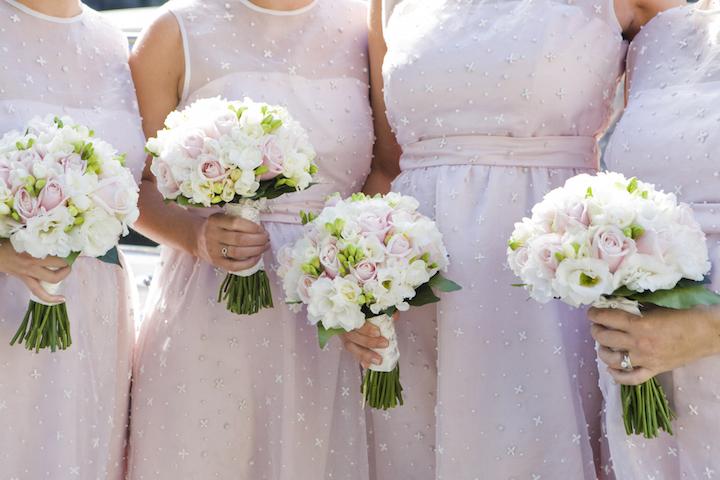 4人のピンクのワンピースを着たブライズメイドが、ブーケを手に記念撮影