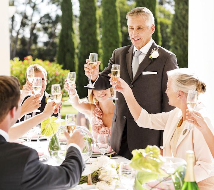 上司のような紳士が、席を立って乾杯のあいさつをしている写真