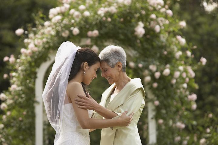 白髪の年配の女性と新婦が、おでこをつけて喜びを分かち合っている写真
