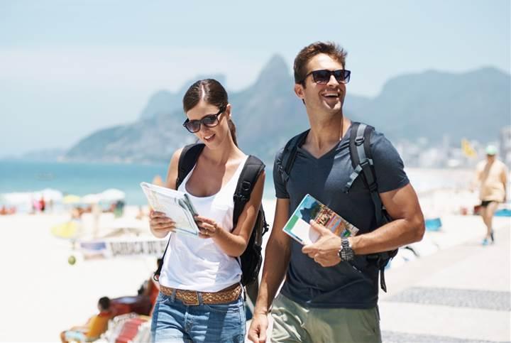 ガイドブック片手にビーチを歩くカップル