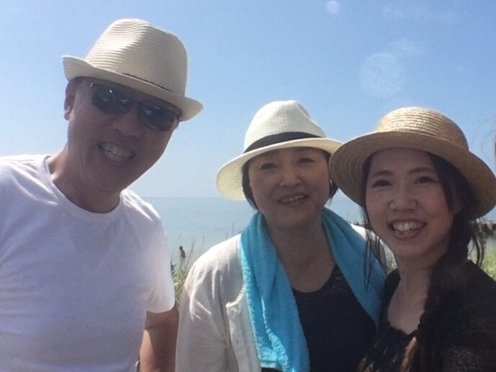 生みを背景に、カンカン帽をかぶった家族写真