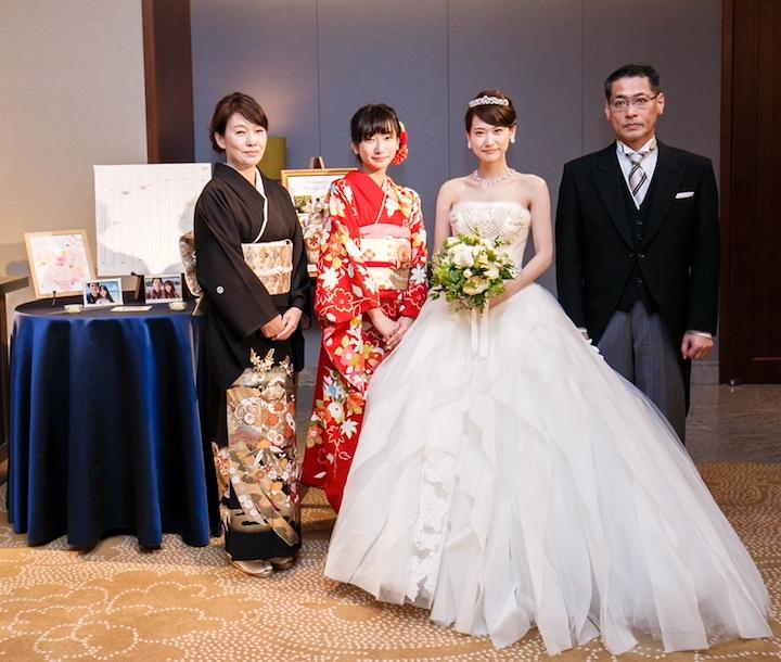 式当日、父母と妹と記念写真。新婦は白ドレス、妹は着物。